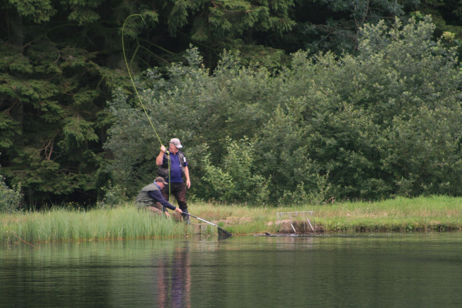 Two men fly fishing, one with a net, the other with a rod