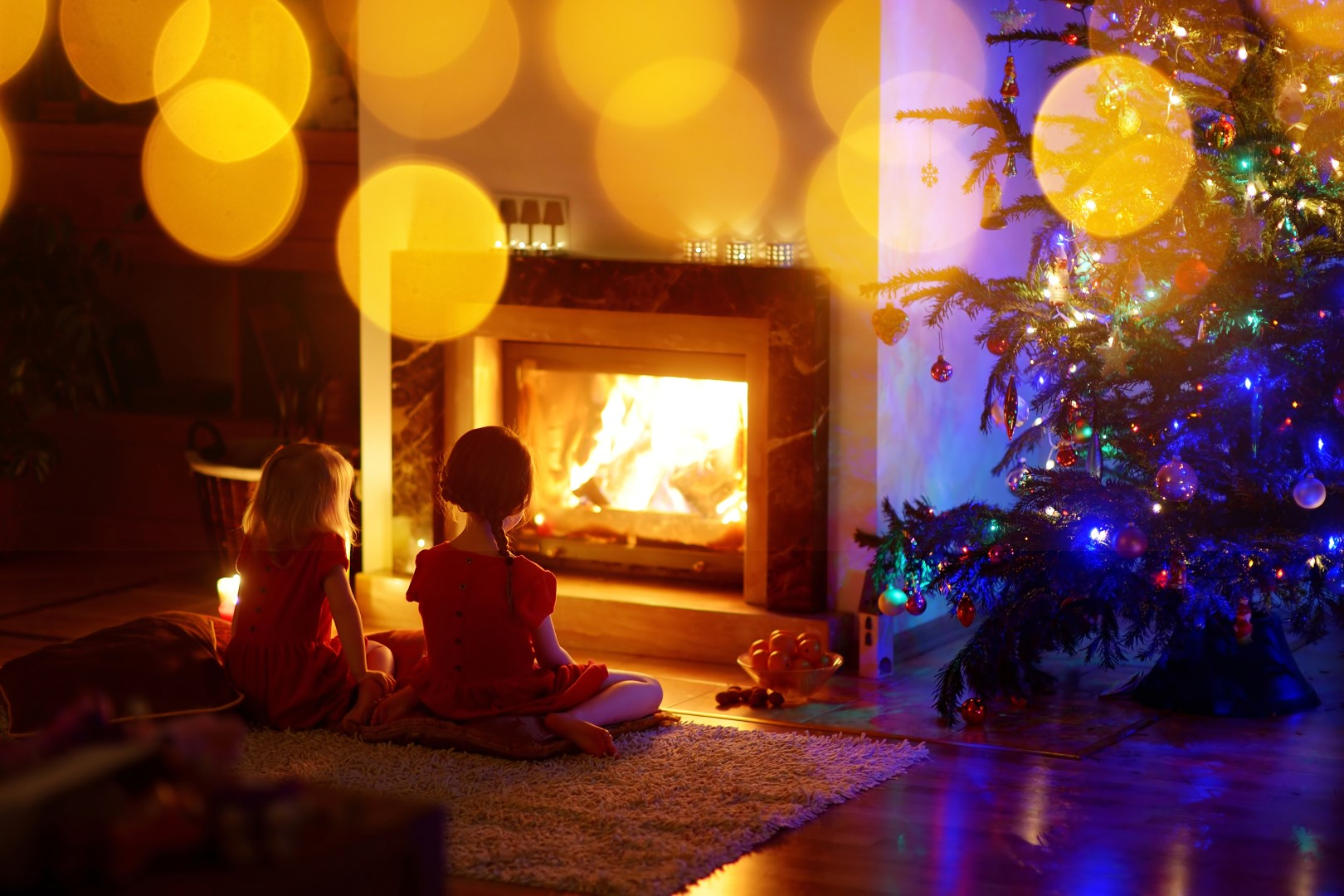 Two young girls in by the Christmas tree in front of the warming fire